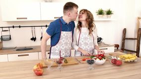 Un hombre ayuda a una cena del cocinero de la mujer en la cocina de la casa almacen de metraje de vídeo