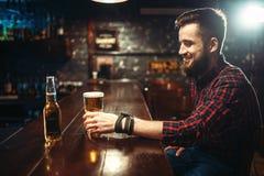 Un hombre barbudo bebe la cerveza en el contador de la barra imagenes de archivo