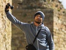 Un hombre barbudo en un sombrero hecho punto se opone a la pared en la fortaleza con una cámara en su mano y a un bolso para la c foto de archivo