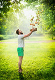 Un hombre barbudo en un prado verde lanza manzanas de cesta en un fondo el fondo natural solar Foto de archivo libre de regalías