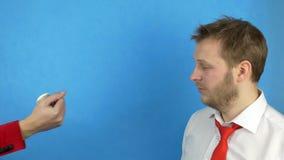 Un hombre barbudo en una camisa y un lazo blancos compra los cigarrillos para los dólares del dinero, el concepto de revender los almacen de metraje de vídeo