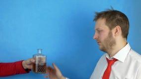 Un hombre barbudo en una camisa y un lazo blancos se aferra al jefe del problema, y compra alcohol para el dinero, fondo azul almacen de metraje de vídeo