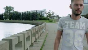 Un hombre barbudo en una camiseta y vaqueros camina a lo largo de la costa en el centro de ciudad almacen de video