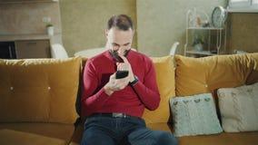 Un hombre barbudo feliz está haciendo un trato o un triunfo acertado con el teléfono y disfruta en casa Freelancer u hombre de ne almacen de video