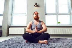 Un hombre barbudo gordo divertido en ropa de los deportes hace yoga en el cuarto imagenes de archivo