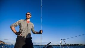 Un hombre barbudo hermoso en gafas de sol en un barco en un río o un lago Individuo feliz hermoso que nada en un barco en un otoñ fotografía de archivo libre de regalías