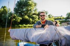 Un hombre barbudo hermoso en gafas de sol en un barco en un r?o o un lago Individuo feliz hermoso que nada en un barco en un oto? imágenes de archivo libres de regalías