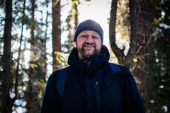 Un hombre barbudo joven camina a través del bosque y sonríe mirándole imagen de archivo