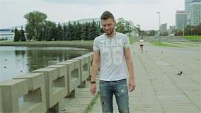 Un hombre barbudo joven salta de la cerca concreta del río y de caminar a lo largo de la acera metrajes