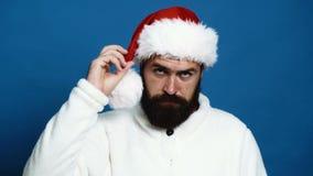 Un hombre barbudo un sombrero rojo del Año Nuevo que lleva en un fondo azul Concepto de celebración del Año Nuevo almacen de video