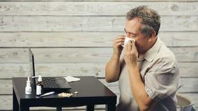 Un hombre barbudo trabaja en el ordenador y las toses almacen de video