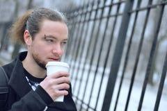 Un hombre bebe el café de una taza en la calle Imágenes de archivo libres de regalías