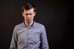 Un hombre blanco cabelludo oscuro con una cara de la expresión de la desconfianza imagen de archivo libre de regalías