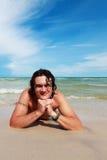 Un hombre blanco joven, mintiendo en una playa arenosa. Fotos de archivo libres de regalías
