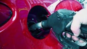 Un hombre bombea el combustible en un coche en una estación de bomba almacen de metraje de vídeo