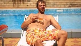 Un hombre borracho en pantalones cortos que bebe la cerveza por la piscina almacen de video