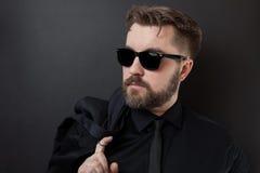 Un hombre brutal con una barba y un peinado elegante en una camisa y un lazo negros está sosteniendo chaqueta Hombre de negocios  imagen de archivo