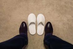 Un hombre cambia sus zapatos, saca sus zapatos, él lleva los deslizadores blancos imagenes de archivo