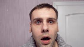 Un hombre cambia una expresión seria en un estúpido y sorprendida con los ojos que bombean y la boca abierta almacen de metraje de vídeo