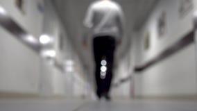 Un hombre camina abajo del pasillo Fondo enmascarado Hombre joven que camina abajo del pasillo largo almacen de video
