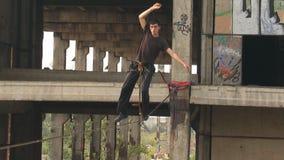 Un hombre camina en una cuerda en una altura en un emplazamiento de la obra abandonado almacen de video