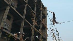 Un hombre camina en una cuerda en una altura en un emplazamiento de la obra abandonado almacen de metraje de vídeo