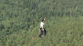 Un hombre camina en una cuerda estirada en una altitud entre dos picos en la reserva de naturaleza siberiana Stolby metrajes