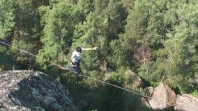Un hombre camina en una cuerda estirada en una altitud entre dos picos en la reserva de naturaleza siberiana Stolby almacen de metraje de vídeo
