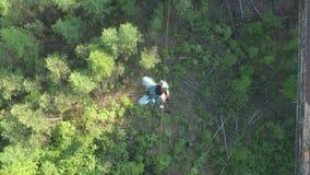Un hombre camina en una cuerda estirada en una altitud entre dos picos en la reserva de naturaleza siberiana Stolby almacen de video