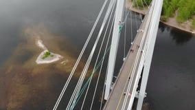 Un hombre camina en una cuerda estirada entre las ayudas del puente en la mucha altitud almacen de metraje de vídeo