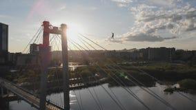 Un hombre camina en una cuerda estirada entre las ayudas del puente en la mucha altitud metrajes