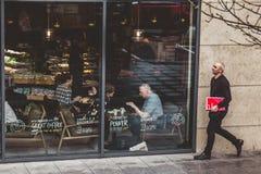 Un hombre camina exterior un ver a través del café donde la gente se está sentando y el hablar imagen de archivo libre de regalías