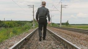 Un hombre camina por el carril metrajes
