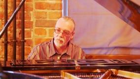 Un hombre canoso con una cola sobre sus vidrios que llevan principales juega entusiasta y cuidadosamente el piano en un jazz metrajes