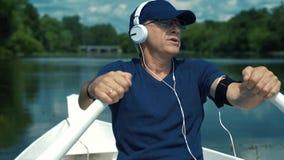 Un hombre canoso delgado en auriculares blancos, un casquillo azul, una camiseta y los vidrios remando los remos en un barco blan metrajes