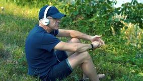 Un hombre canoso delgado en auriculares blancos, una camiseta azul, un casquillo y vidrios se sienta en la hierba verde en el ban almacen de video