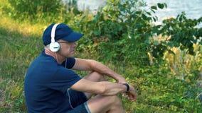 Un hombre canoso delgado en auriculares blancos, una camiseta azul, un casquillo y vidrios se sienta en la hierba verde en el ban metrajes