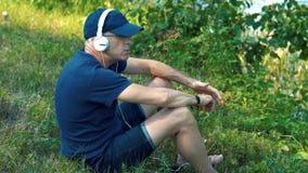 Un hombre canoso delgado en auriculares blancos, una camiseta azul, un casquillo y vidrios se sienta en la hierba verde en el ban almacen de metraje de vídeo