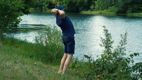 Un hombre canoso delgado en una camiseta, un casquillo y vidrios azules camina descalzo en la hierba verde en la orilla del río e almacen de video