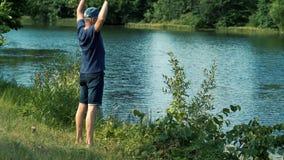 Un hombre canoso delgado en una camiseta, un casquillo y vidrios azules camina descalzo en la hierba verde en la orilla del río e metrajes