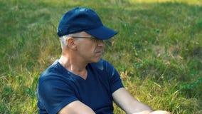 Un hombre canoso en una camiseta azul, un casquillo y los vidrios delgados, serios se sienta en la hierba verde en el bosque en u almacen de metraje de vídeo
