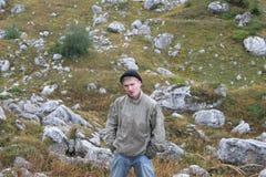 Un hombre cansó y mojó en viajar entre piedras y arbustos Hombre Imagen de archivo