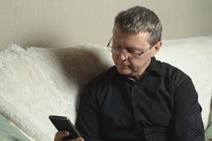 Un hombre cansado en una camisa negra está mirando la pantalla de un smartphone mientras que se sienta en un sofá fotos de archivo libres de regalías