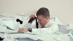 Un hombre cansado joven se sienta en una pila de papeles y firma documentos Debido al número de documentos, oficinista no pueda almacen de video