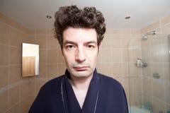 Un hombre cansado que mira en el espejo fotografía de archivo