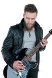 Un hombre carismático con una barba, en una chaqueta de cuero, tocando una guitarra eléctrica, en un fondo aislado blanco Marco h Fotografía de archivo libre de regalías