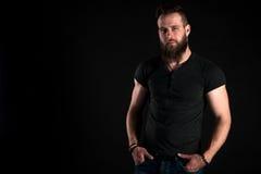 Un hombre carismático y elegante con una barba se coloca integral en un fondo aislado negro Marco horizontal Foto de archivo