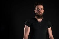 Un hombre carismático y elegante con una barba se coloca integral en un fondo aislado negro Marco horizontal Imagen de archivo