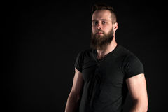 Un hombre carismático y elegante con una barba se coloca integral en un fondo negro Marco horizontal Fotografía de archivo libre de regalías