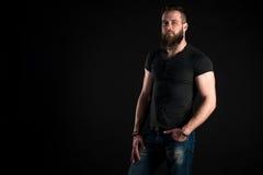 Un hombre carismático y elegante con una barba se coloca integral en un fondo negro Marco horizontal Imágenes de archivo libres de regalías